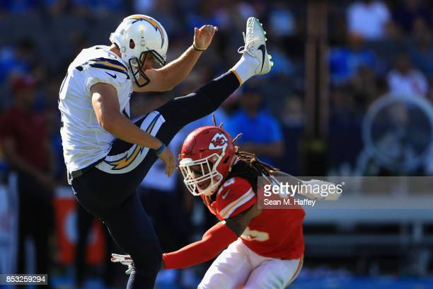 Drew Kaser of the Los Angeles Chargers punts the ball under pressure from Terrance Smith of the Kansas City Chiefs during the second half of a game...