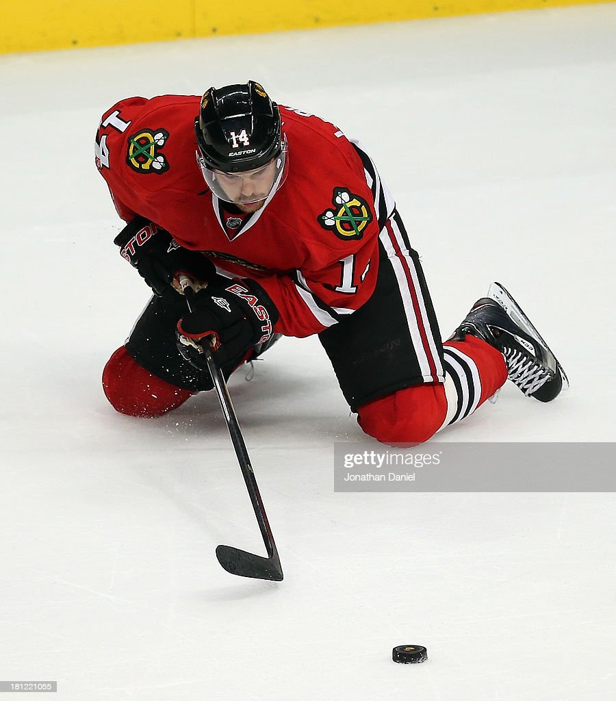 Drew LeBlanc #14 of the Chicago Blackhawks hits the ice trying to control the puck against the Pittsburgh Penguins during an exhibition game at United Center on September 19, 2013 in Chicago, Illinois. The Penguins defeated the Blackhawks 4-3 in a shootout.