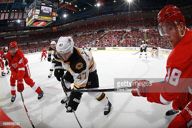 Drew Miller and Joakim Andersson of the Detroit Red Wings battle with Torey Krug of the Boston Bruins in the corner for the puck during the NHL...