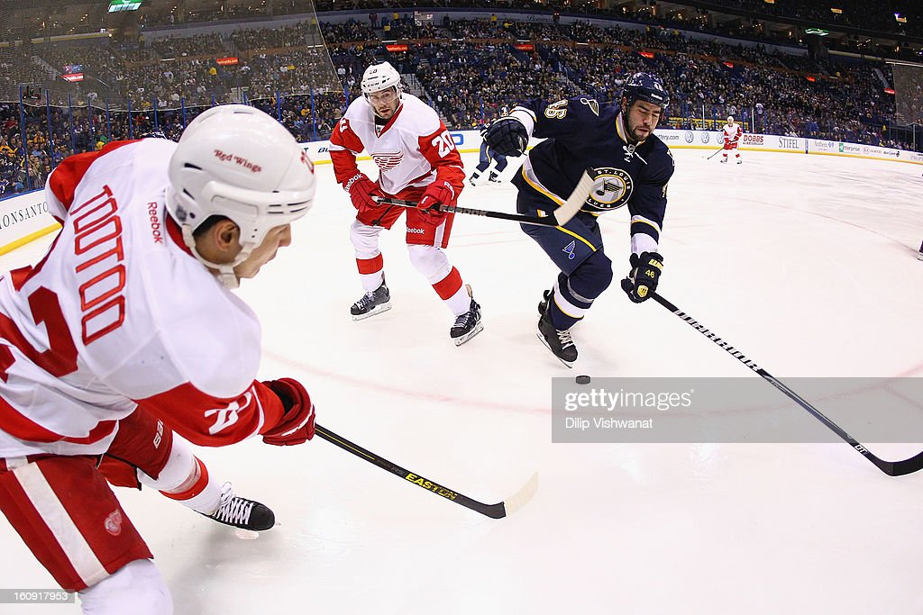 Drew Miller #20 and <a gi-track='captionPersonalityLinkClicked' href=/galleries/search?phrase=Jordin+Tootoo&family=editorial&specificpeople=203013 ng-click='$event.stopPropagation()'>Jordin Tootoo</a> #22 both of the Detroit Red Wings look to clear the puck against <a gi-track='captionPersonalityLinkClicked' href=/galleries/search?phrase=Roman+Polak&family=editorial&specificpeople=2109482 ng-click='$event.stopPropagation()'>Roman Polak</a> #46 of the St. Louis Blues at the Scottrade Center on February 7, 2013 in St. Louis, Missouri.