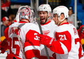 Drew Miller and Tomas Tatar congratulate teammate Jimmy Howard of the Detroit Red Wings on their win and shut out against the New York Islanders at...