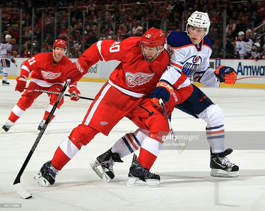 Drew Miller #20 of the Detroit Red Wings and <a gi-track='captionPersonalityLinkClicked' href=/galleries/search?phrase=Ryan+Nugent-Hopkins&family=editorial&specificpeople=7144190 ng-click='$event.stopPropagation()'>Ryan Nugent-Hopkins</a> #93 of the Edmonton Oilers battle for the puck during a NHL game at Joe Louis Arena on February 9, 2013 in Detroit, Michigan.
