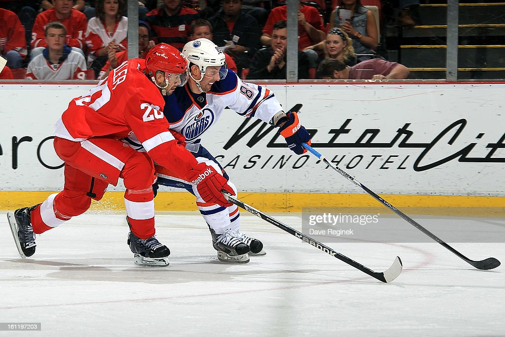 Drew Miller #20 of the Detroit Red Wings and <a gi-track='captionPersonalityLinkClicked' href=/galleries/search?phrase=Sam+Gagner&family=editorial&specificpeople=4042961 ng-click='$event.stopPropagation()'>Sam Gagner</a> #89 of the Edmonton Oilers battle for the puck during a NHL game at Joe Louis Arena on February 9, 2013 in Detroit, Michigan. Detroit defeated Edmonton 2-1