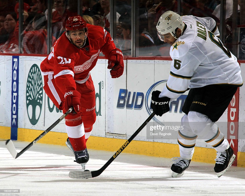 Drew Miller #20 of the Detroit Red Wings and Trevor Daly #6 of the Dallas Stars reach for the puck during an NHL game at Joe Louis Arena on January 29, 2013 in Detroit, Michigan. Detroit defeated Dallas 4-1