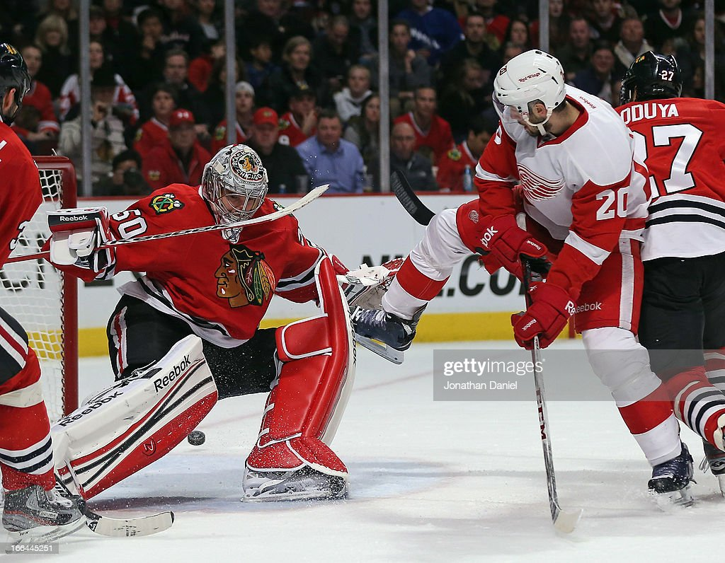 Drew Miller #20 of the Detroit Red Wings attempts a shot against <a gi-track='captionPersonalityLinkClicked' href=/galleries/search?phrase=Corey+Crawford&family=editorial&specificpeople=818935 ng-click='$event.stopPropagation()'>Corey Crawford</a> #50 of the Chicago Blackhawks at the United Center on April 12, 2013 in Chicago, Illinois.