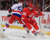 Drew Miller of the Detroit Red Wings battles for the puck with Connor Carrick of the Washington Capitals during an NHL game on January 31 2014 at Joe...