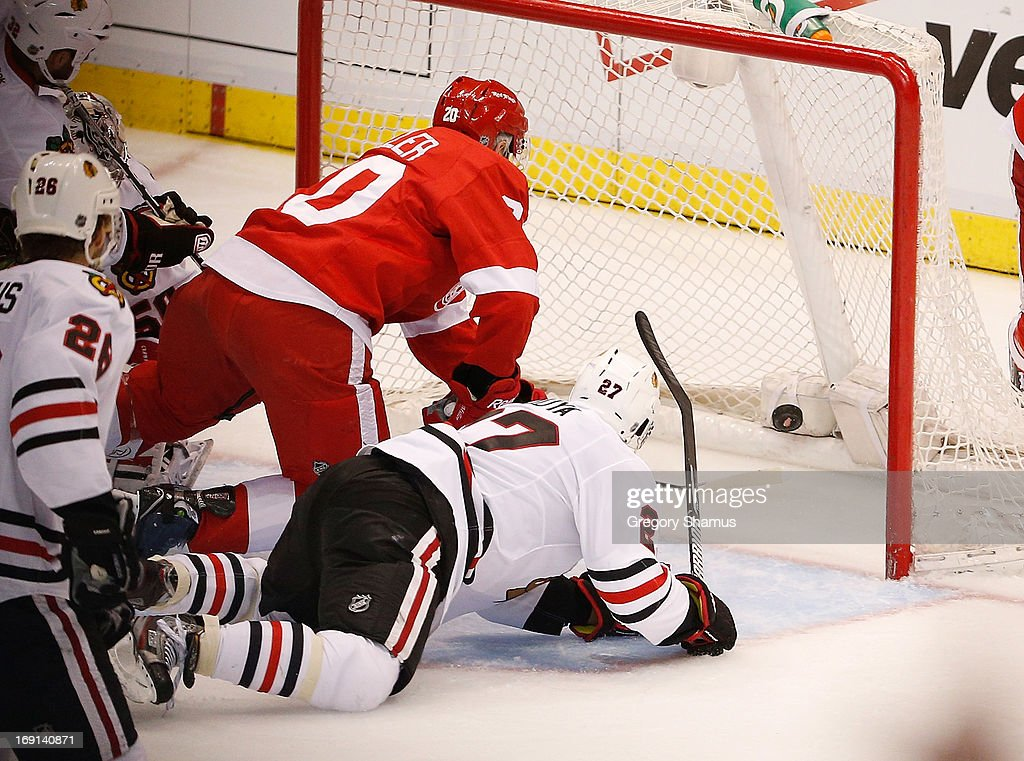 Drew Miller #20 of the Detroit Red Wings beats <a gi-track='captionPersonalityLinkClicked' href=/galleries/search?phrase=Johnny+Oduya&family=editorial&specificpeople=3944055 ng-click='$event.stopPropagation()'>Johnny Oduya</a> #27 of the Chicago Blackhawks to the puck to score a second period goal in Game Three of the Western Conference Semifinals during the 2013 NHL Stanley Cup Playoffs at Joe Louis Arena on May 20, 2013 in Detroit, Michigan.