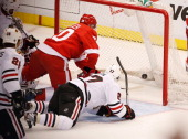 Drew Miller of the Detroit Red Wings beats Johnny Oduya of the Chicago Blackhawks to the puck to score a second period goal in Game Three of the...