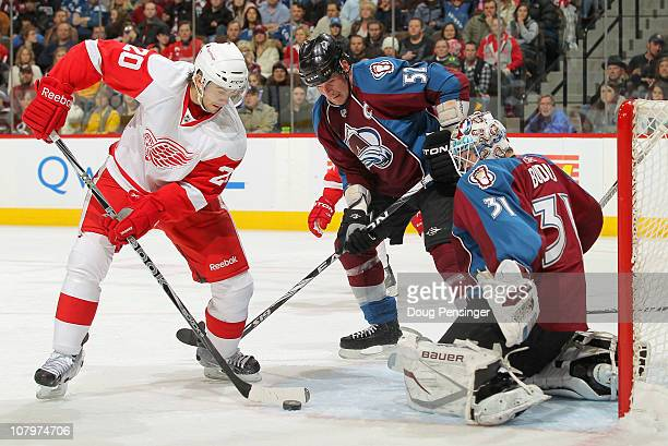 Drew Miller of the Detroit Red Wings collects the puck as Adam Foote of the Colorado Avalanche helps goalie Peter Budaj of the Avalanche defend the...