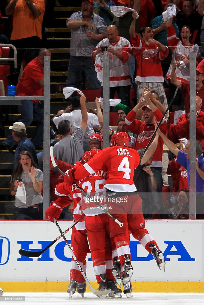 Drew Miller #20 of the Detroit Red Wings gets gets jumped on by temates <a gi-track='captionPersonalityLinkClicked' href=/galleries/search?phrase=Jakub+Kindl&family=editorial&specificpeople=716743 ng-click='$event.stopPropagation()'>Jakub Kindl</a> #4, <a gi-track='captionPersonalityLinkClicked' href=/galleries/search?phrase=Carlo+Colaiacovo&family=editorial&specificpeople=234960 ng-click='$event.stopPropagation()'>Carlo Colaiacovo</a> #28 and Corey Emmerton #25 after scoring a goal during Game Three of the Western Conference Semifinals against the Chicago Blackhawks during the 2013 NHL Stanley Cup Playoffs at Joe Louis Arena on May 20, 2013 in Detroit, Michigan.