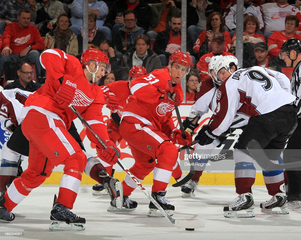 Drew Miller #20 of the Detroit Red Wings handles the puck after teamate Valterri Fillpula #51 beats <a gi-track='captionPersonalityLinkClicked' href=/galleries/search?phrase=Matt+Duchene&family=editorial&specificpeople=4819304 ng-click='$event.stopPropagation()'>Matt Duchene</a> #9 of the Colorado Avalanche on a faceoff during a NHL game at Joe Louis Arena on April 1, 2013 in Detroit, Michigan.