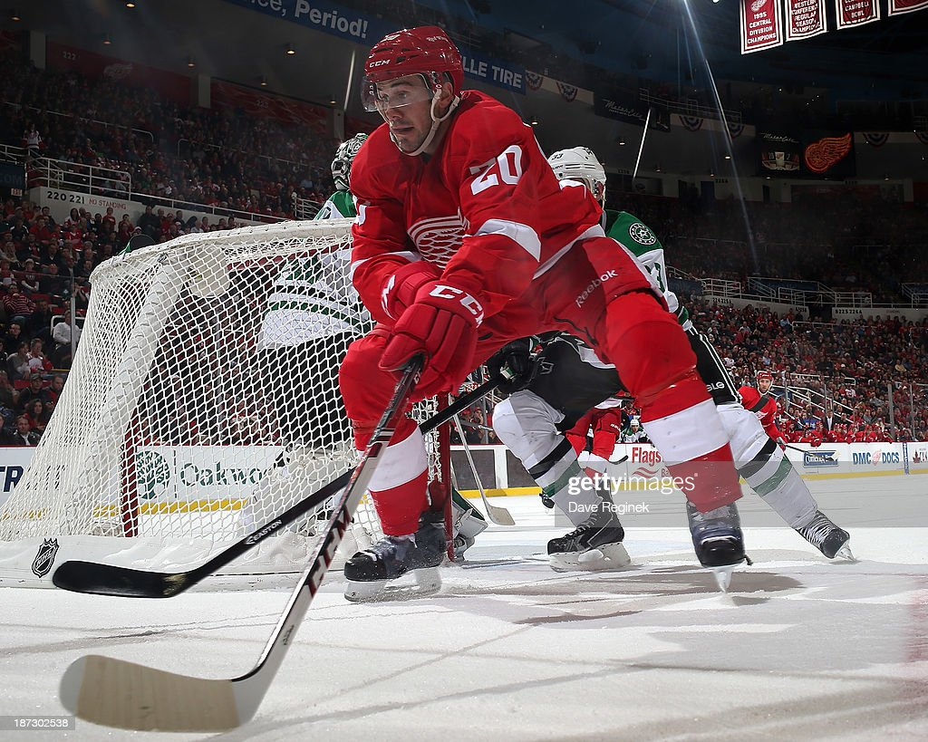 Drew Miller #20 of the Detroit Red Wings handles the puck behind the net as <a gi-track='captionPersonalityLinkClicked' href=/galleries/search?phrase=Alex+Goligoski&family=editorial&specificpeople=791866 ng-click='$event.stopPropagation()'>Alex Goligoski</a> #33 of the Dallas Stars defends him during an NHL game at Joe Louis Arena on November 7, 2013 in Detroit, Michigan. Dallas defeated Detroit 4-3 in OT