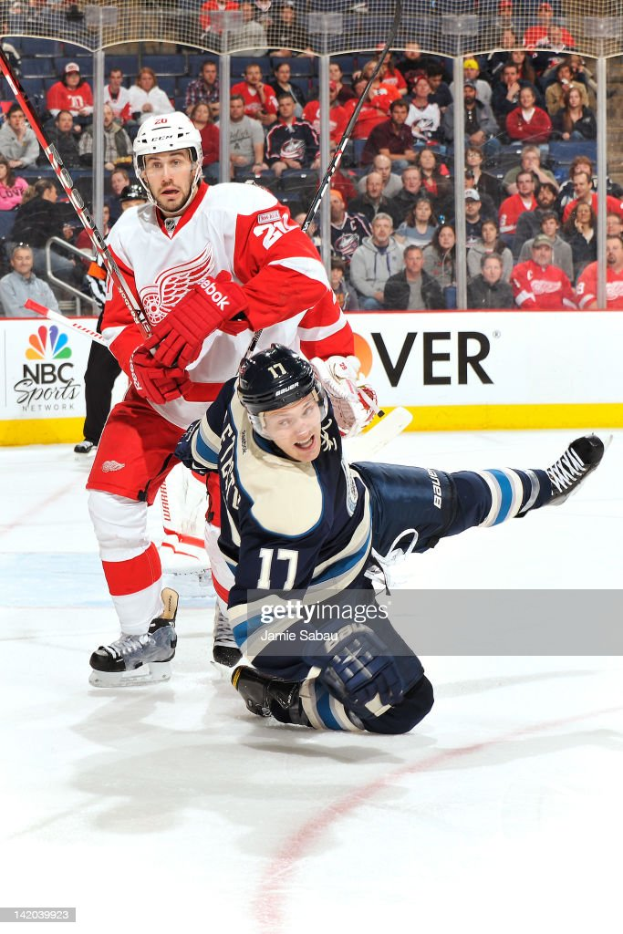 Drew Miller of the Detroit Red Wings knocks down Mark Letestu of the Columbus Blue Jackets while chasing after a loose puck during the second period...
