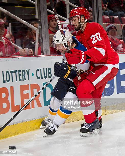 Drew Miller of the Detroit Red Wings puts a body check on Chris Butler of the St Louis Blues during a NHL game on March 22 2015 at Joe Louis Arena in...