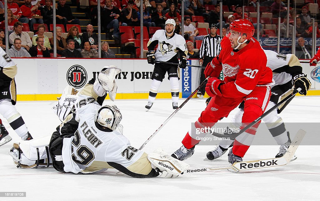 Drew Miller #20 of the Detroit Red Wings scores a second period goal past the diving <a gi-track='captionPersonalityLinkClicked' href=/galleries/search?phrase=Marc-Andre+Fleury&family=editorial&specificpeople=233779 ng-click='$event.stopPropagation()'>Marc-Andre Fleury</a> #29 of the Pittsburgh Penguins during a pre season game at Joe Louis Arena on September 25, 2013 in Detroit, Michigan.