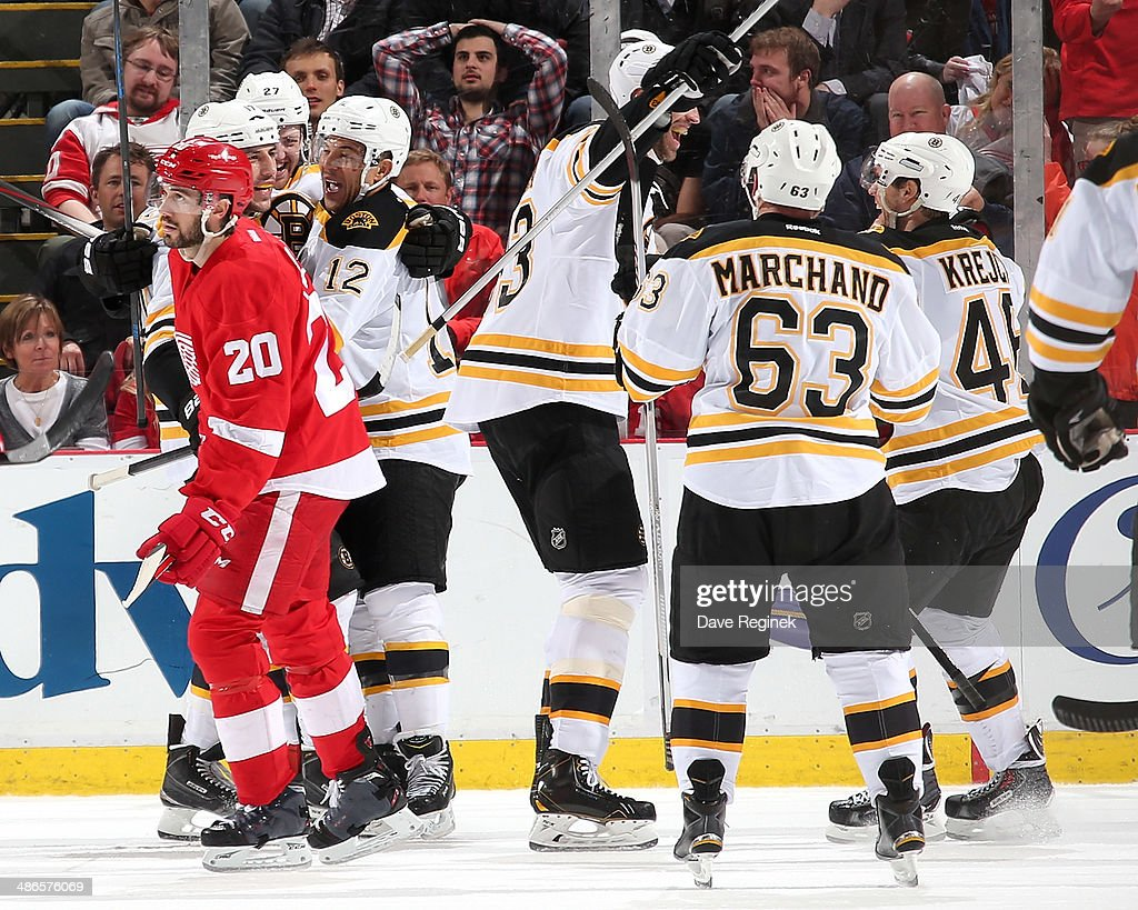 Drew Miller #20 of the Detroit Red Wings skates away as members of the Boston Bruins celebrate with teammate <a gi-track='captionPersonalityLinkClicked' href=/galleries/search?phrase=Jarome+Iginla&family=editorial&specificpeople=201792 ng-click='$event.stopPropagation()'>Jarome Iginla</a> #12 after scoring the game winning goal in overtime of Game Four of the First Round of the 2014 Stanley Cup Playoffs on April 24, 2014 at Joe Louis Arena in Detroit, Michigan. Bruins defeated Detroit 3-2 in OT