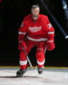 Drew Miller of the Detroit Red Wings skates onto the ice after being introduced for the pregame ceremonies before an NHL game against the Buffalo...