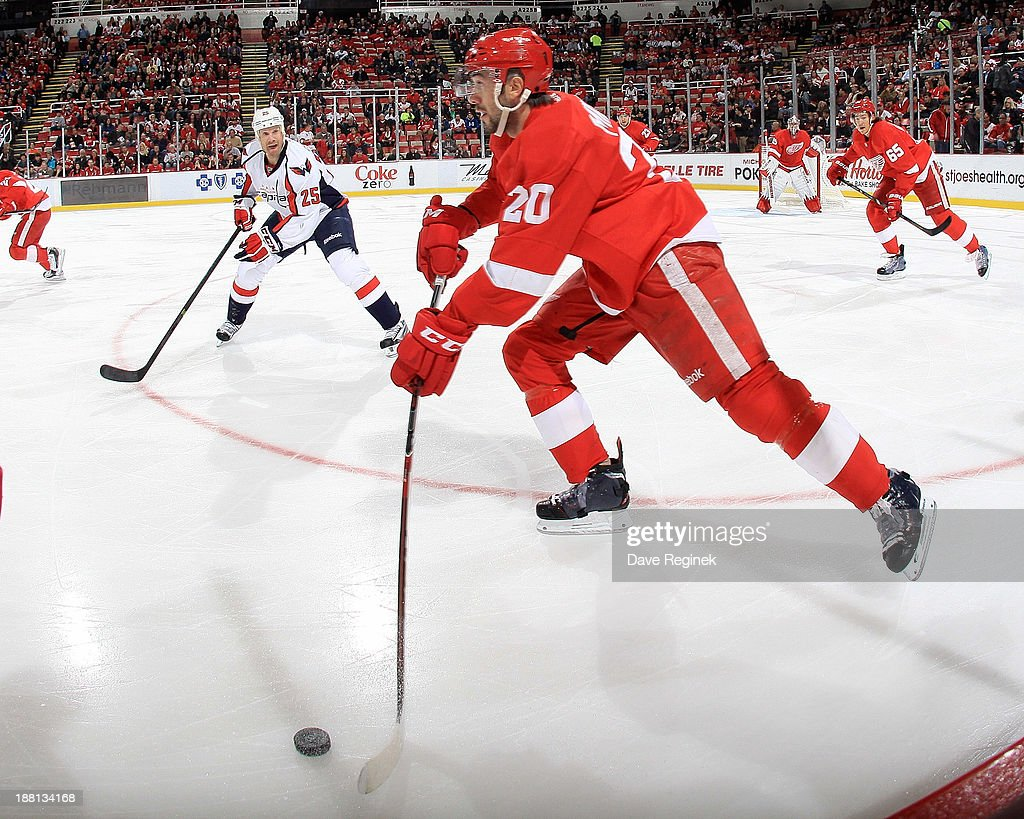 Drew Miller #20 of the Detroit Red Wings skates with the puck as <a gi-track='captionPersonalityLinkClicked' href=/galleries/search?phrase=Jason+Chimera&family=editorial&specificpeople=211264 ng-click='$event.stopPropagation()'>Jason Chimera</a> #25 of the Washington Capitals defends along the boards during an NHL game at Joe Louis Arena on November 15, 2013 in Detroit, Michigan.