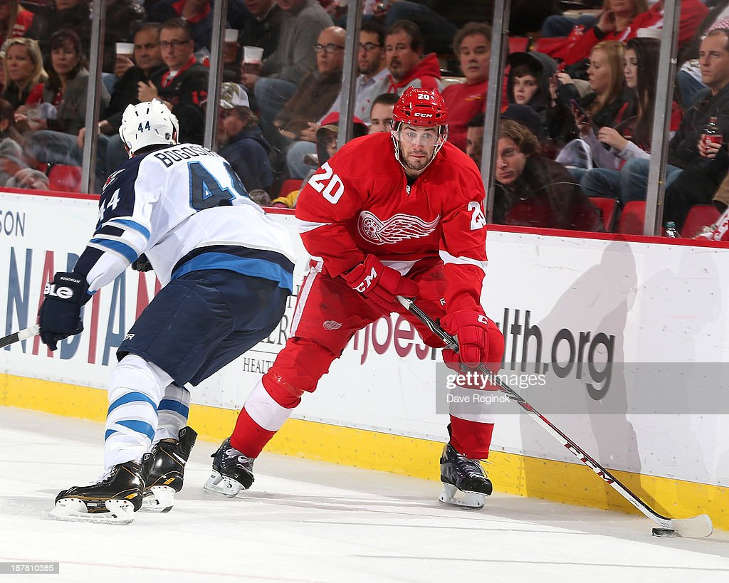 Drew Miller #20 of the Detroit Red Wings skates with the puck as <a gi-track='captionPersonalityLinkClicked' href=/galleries/search?phrase=Zach+Bogosian&family=editorial&specificpeople=4195061 ng-click='$event.stopPropagation()'>Zach Bogosian</a> #44 of the Winnipeg Jets defends him during an NHL game at Joe Louis Arena on November 12, 2013 in Detroit, Michigan.