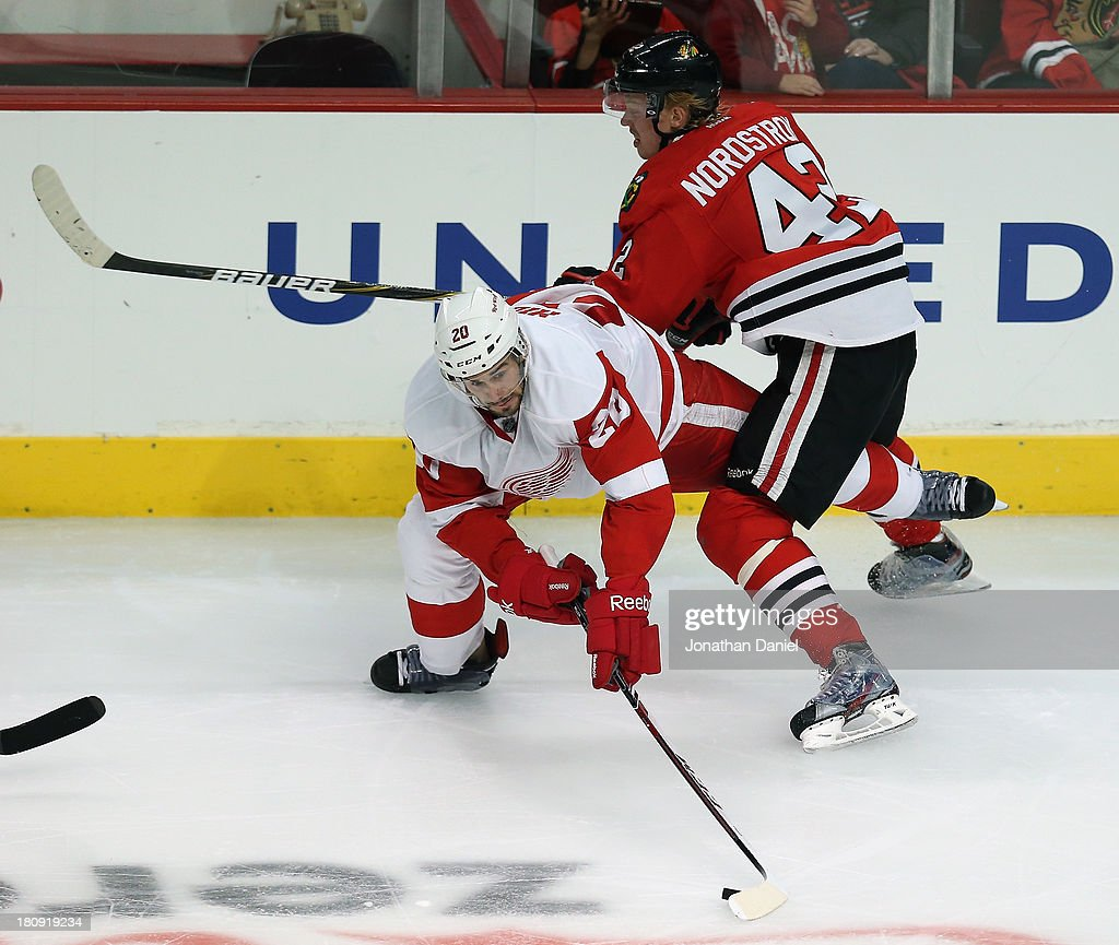 Drew Miller #20 of the Detroit Red Wings tries to control the puck as he is hit by Joakim Nordstrom #42 of the Chicago Blackhawks during an exhibition game at United Center on September 17, 2013 in Chicago, Illinois. The Blackhawks defeated the Red Wings 2-0.