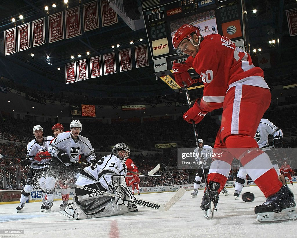 Drew Miller #20 of the Detroit Red Wings tries to find the puck in his skates as Jonathan Quick #32 of the Los Angeles Kings guards the net during a NHL game at Joe Louis Arena on February 10, 2013 in Detroit, Michigan. The Wings won 3-2