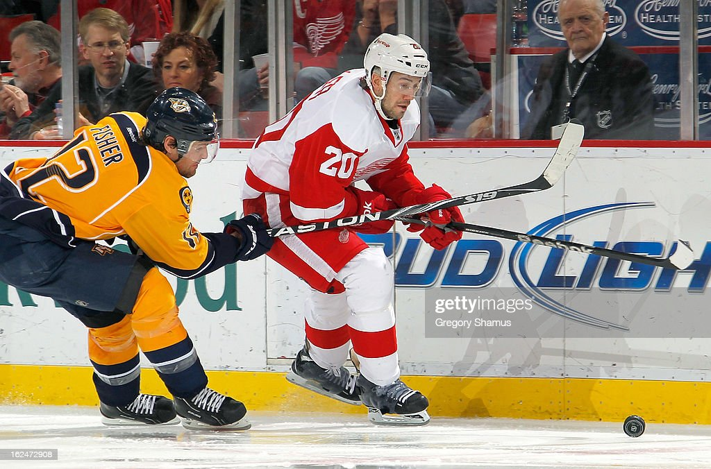 Drew Miller #20 of the Detroit Red Wings tries to get around the stick of <a gi-track='captionPersonalityLinkClicked' href=/galleries/search?phrase=Mike+Fisher+-+Ice+Hockey+Player&family=editorial&specificpeople=204732 ng-click='$event.stopPropagation()'>Mike Fisher</a> #12 of the Nashville Predators during the third period at Joe Louis Arena on February 23, 2013 in Detroit, Michigan. Detroit won the game 4-0.