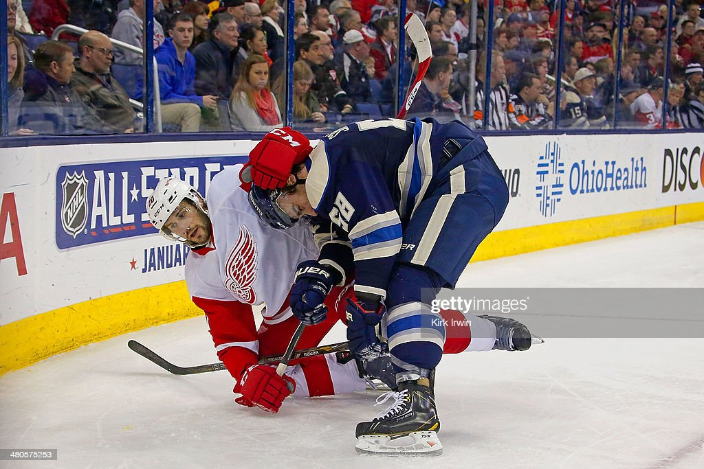 Drew Miller #20 of the Detroit Red Wings wrestles with <a gi-track='captionPersonalityLinkClicked' href=/galleries/search?phrase=David+Savard&family=editorial&specificpeople=4630692 ng-click='$event.stopPropagation()'>David Savard</a> #58 of the Columbus Blue Jackets after being knocked to the ice during the third period on March 25, 2014 at Nationwide Arena in Columbus, Ohio. Columbus defeated Detroit 4-2.