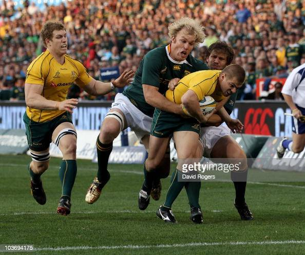 Drew Mitchell of Australia is tackled short of the tryline by Schalk Burger and Frans Steyn during the 2010 TriNations match between the South...