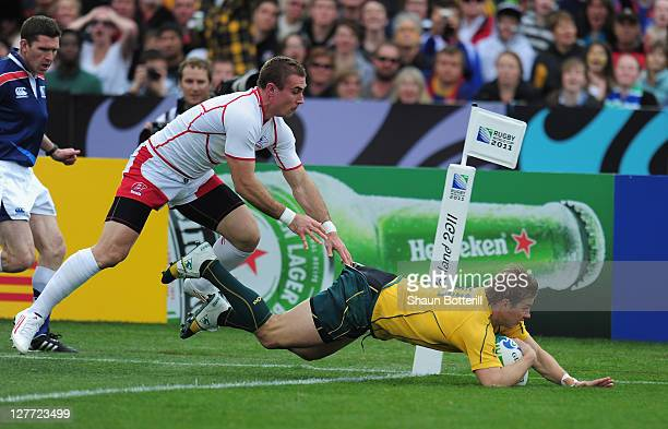 Drew Mitchell of Australiabreaks through the tackle of Vladimir Ostroushko of Russia to score during the IRB 2011 Rugby World Cup Pool C match...