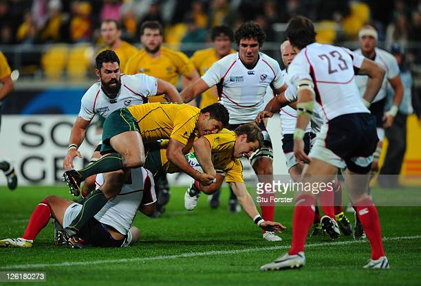 Drew Mitchell of the Wallabies is driven over the line by teammate Anthony Fainga'a to score his team's fifth try during match 23 of the IRB 2011...