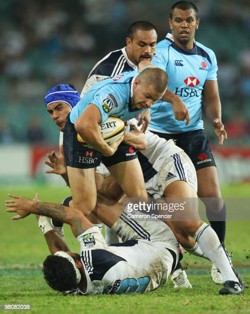 Drew Mitchell of the Waratahs is tackled during the round seven Super 14 match between the Waratahs and the Blues at Sydney Football Stadium on March...
