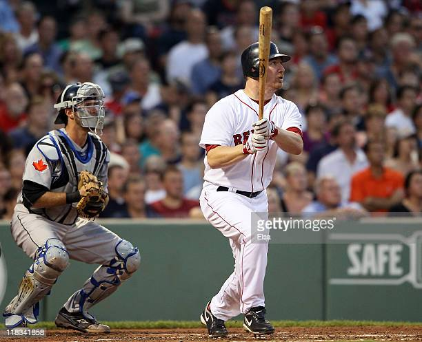 D Drew of the Boston Red Sox hits a single as JP Arencibia of the Toronto Blue Jays defends in the fourth inning on July 6 2011 at Fenway Park in...