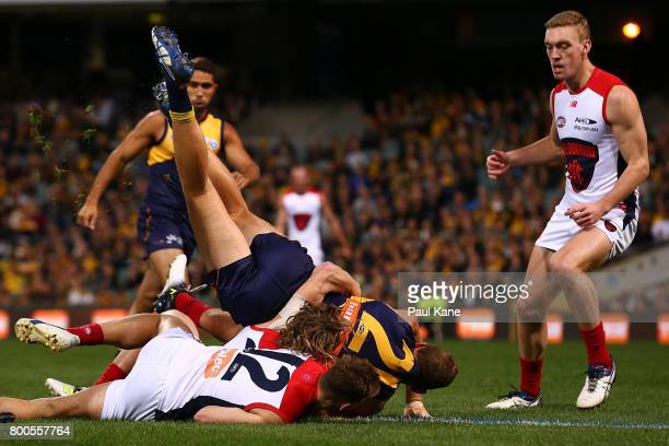 Drew Petrie of the Eagles gets tackled by Jayden Hunt and Dom Tyson of the Demons during the round 14 AFL match between the West Coast Eagles and the...