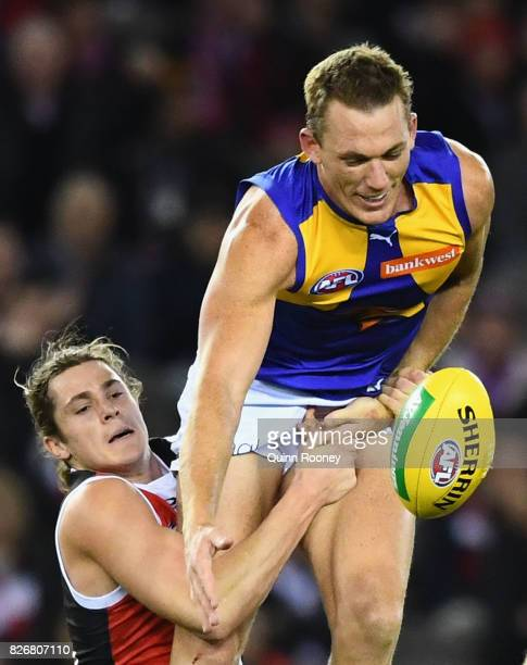 Drew Petrie of the Eagles handballs whilst being tackled by Jack Steele of the Saints during the round 20 AFL match between the St Kilda Saints and...