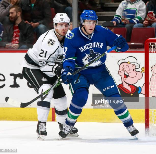 Drew Shore of the Vancouver Canucks is checked by Nick Shore of the Los Angeles Kings during their NHL game at Rogers Arena March 31 2017 in...