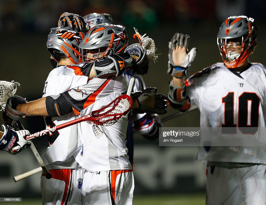 Drew Snider #23 of the Denver Outlaws celebrates with teammates after he scored a goal late in the 4th quarter against the Boston Cannons at Harvard Stadium on May 11, 2013 in Boston, Massachusetts.