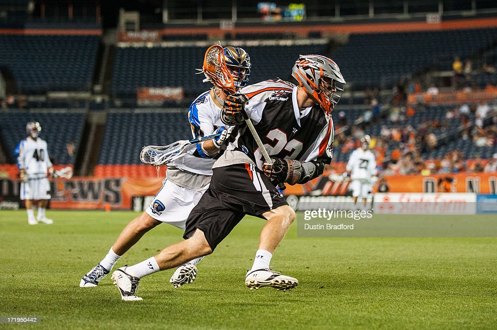 Drew Snider #23 of the Denver Outlaws is covered as he runs the clock out during a game against the Charlotte Hounds during a Major League Lacrosse game at Sports Authority Field at Mile High on June 29, 2013 in Denver, Colorado. The Outlaws beat the Hounds 17-11 and improved to 9-0 on the season.