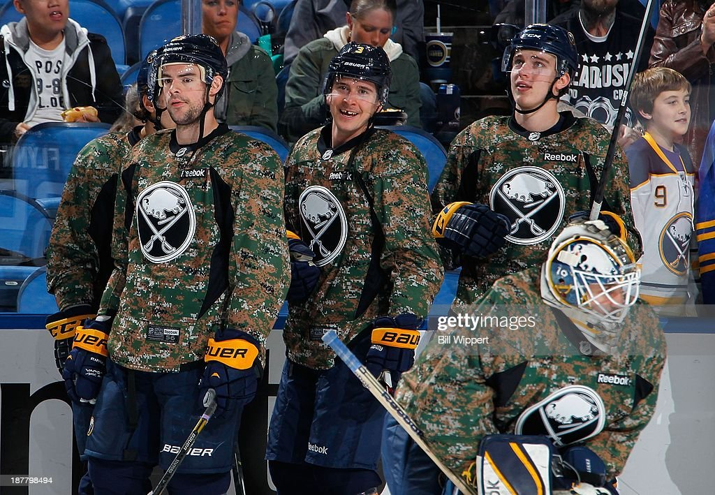 Drew Stafford, Mark Pysyk, Rasmus Ristolainen and goaltender Jhonas Enroth (L-R) of the Buffalo Sabres wear camouflage jerseys while warming up for their game against the Los Angeles Kings on November 12, 2013 at the First Niagara Center in Buffalo, New York.