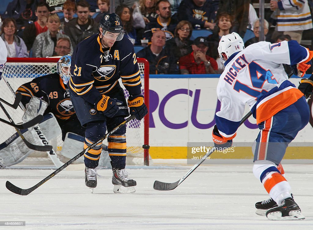 Drew Stafford #21 of the Buffalo Sabres braces to block a shot by Thomas Hickey #14 of the New York Islanders at First Niagara Center on April 13, 2014 in Buffalo, New York.