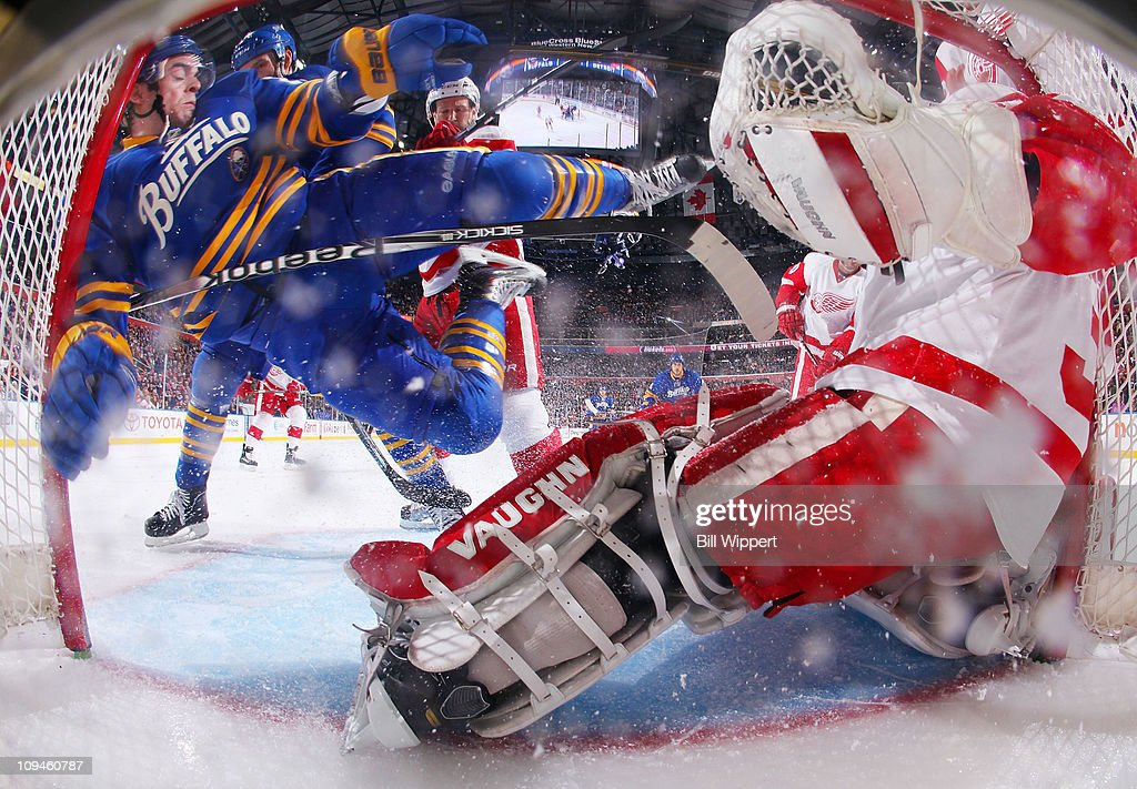 Drew Stafford of the Buffalo Sabres flies through the goal crease of Joey MacDonald of the Detroit Red Wings while being defended by Red Wings...