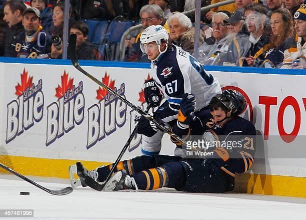 Drew Stafford of the Buffalo Sabres gets checked to the ice by Michael Frolik of the Winnipeg Jets on December 17 2013 at the First Niagara Center in...