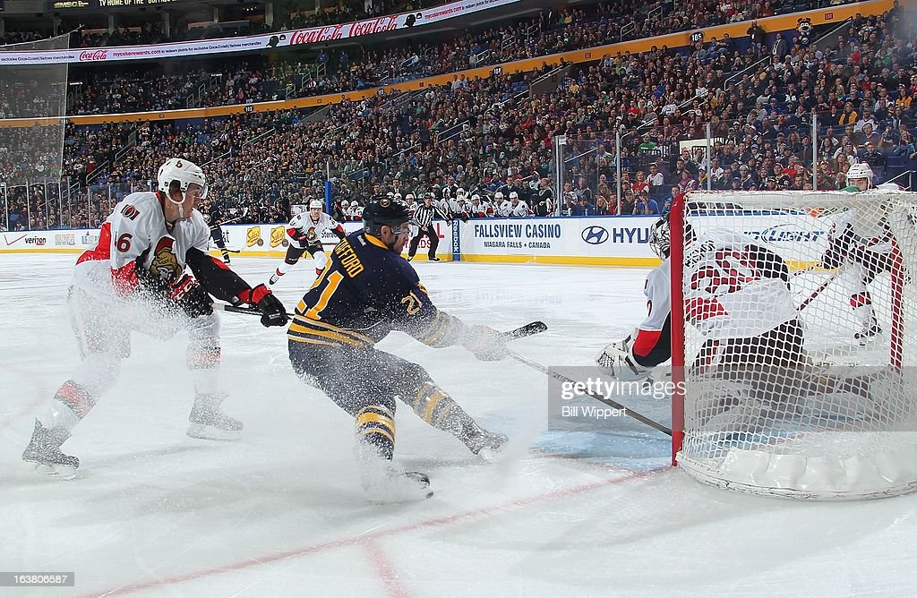 <a gi-track='captionPersonalityLinkClicked' href=/galleries/search?phrase=Drew+Stafford&family=editorial&specificpeople=220617 ng-click='$event.stopPropagation()'>Drew Stafford</a> #21 of the Buffalo Sabres goes to the front of the net defended by goaltender <a gi-track='captionPersonalityLinkClicked' href=/galleries/search?phrase=Ben+Bishop&family=editorial&specificpeople=700137 ng-click='$event.stopPropagation()'>Ben Bishop</a> #30 and <a gi-track='captionPersonalityLinkClicked' href=/galleries/search?phrase=Patrick+Wiercioch&family=editorial&specificpeople=5408887 ng-click='$event.stopPropagation()'>Patrick Wiercioch</a> #46 of the Ottawa Senators on March 16, 2013 at the First Niagara Center in Buffalo, New York.