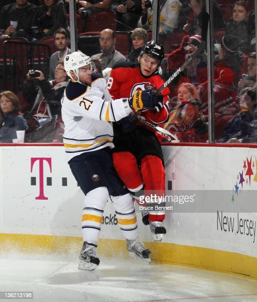 Drew Stafford of the Buffalo Sabres hits Anton Volchenkov of the New Jersey Devils into the boards at the Prudential Center on December 28 2011 in...