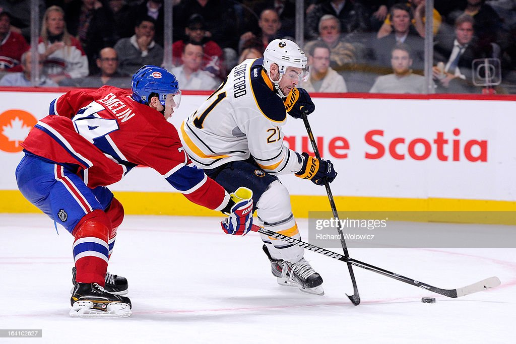 <a gi-track='captionPersonalityLinkClicked' href=/galleries/search?phrase=Drew+Stafford&family=editorial&specificpeople=220617 ng-click='$event.stopPropagation()'>Drew Stafford</a> #21 of the Buffalo Sabres moves the puck past <a gi-track='captionPersonalityLinkClicked' href=/galleries/search?phrase=Alexei+Emelin&family=editorial&specificpeople=723573 ng-click='$event.stopPropagation()'>Alexei Emelin</a> #74 of the Montreal Canadiens during the NHL game at the Bell Centre on March 19, 2013 in Montreal, Quebec, Canada. The Sabres defeated the Canadiens 3-2 in overtime.