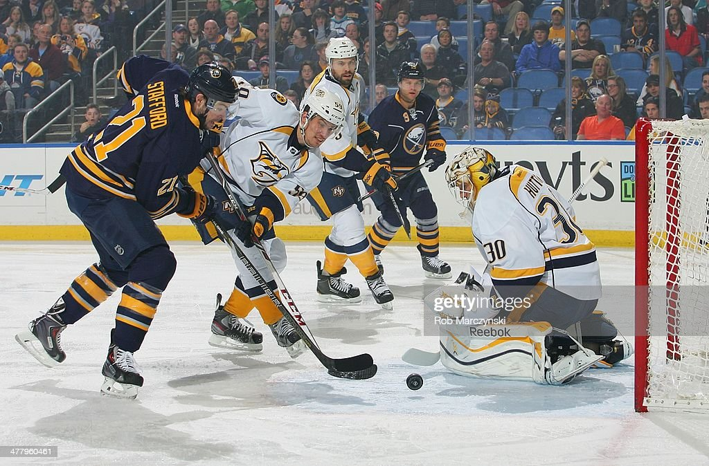 <a gi-track='captionPersonalityLinkClicked' href=/galleries/search?phrase=Drew+Stafford&family=editorial&specificpeople=220617 ng-click='$event.stopPropagation()'>Drew Stafford</a> #21 of the Buffalo Sabres scores a first period goal against #30 <a gi-track='captionPersonalityLinkClicked' href=/galleries/search?phrase=Carter+Hutton&family=editorial&specificpeople=6872781 ng-click='$event.stopPropagation()'>Carter Hutton</a> and Roman Jost #59 of the Nashville Predators. It was Stafford's 500th NHL game played on March 11, 2014 at the First Niagara Center in Buffalo, New York.