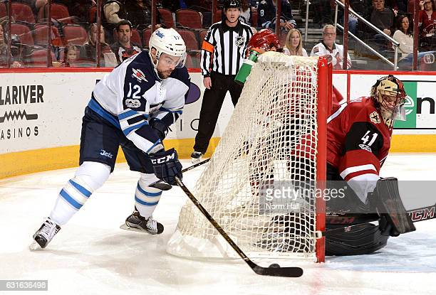 Drew Stafford of the Winnipeg Jets attempts to wrap the puck around the net as Mike Smith of the Arizona Coyotes makes a pad save during the first...