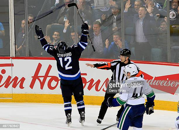 Drew Stafford of the Winnipeg Jets celebrates his second period goal as Matt Bartkowski of the Vancouver Canucks looks on at the MTS Centre on...