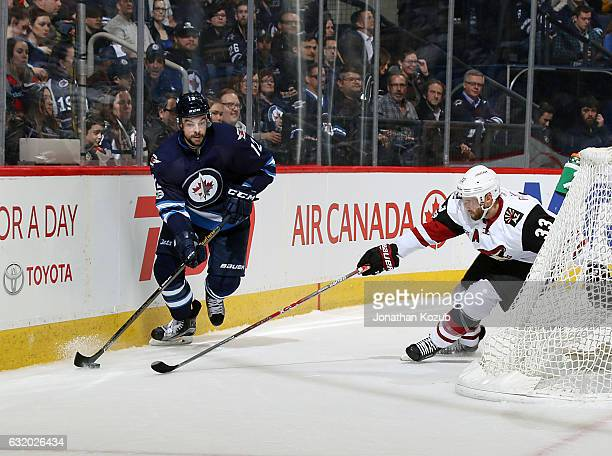 Drew Stafford of the Winnipeg Jets plays the puck along the boards as Alex Goligoski of the Arizona Coyotes defends during second period action at...