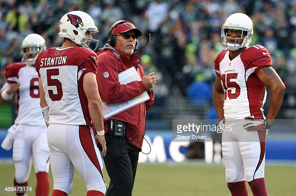 Drew Stanton and Michael Floyd of the Arizona Cardinals talk with head coach Bruce Arians against the Seattle Seahawks during their game at...