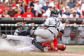 Drew Stubbs of the Cincinnati Reds slides at home plate to score a run in the fifth inning under the tag of Francisco Cervelli of the New York...